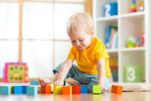 Kleinkind spielt mit Bauklötzen auf dem Boden