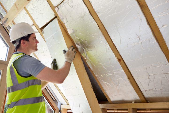 ein arbeiter dämmt das dach